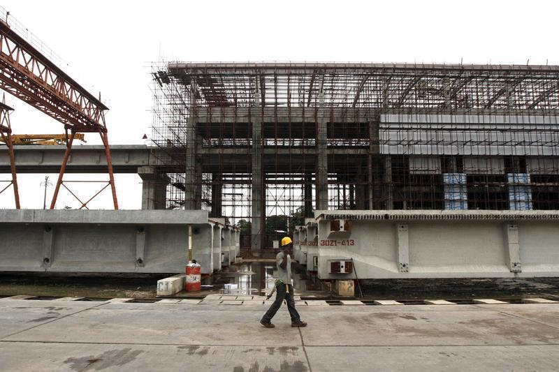 A man walks past a light rail station under construction at the Orile-Iganmu district in Lagos
