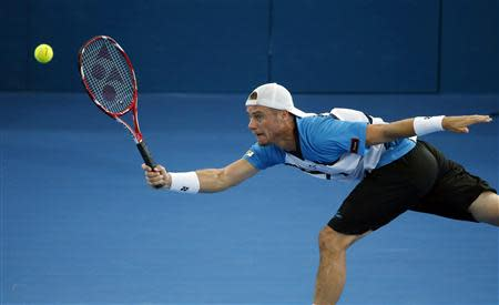 Lleyton Hewitt of Australia lunges for the ball during his men's final match against Roger Federer of Switzerland at the Brisbane International tennis tournament