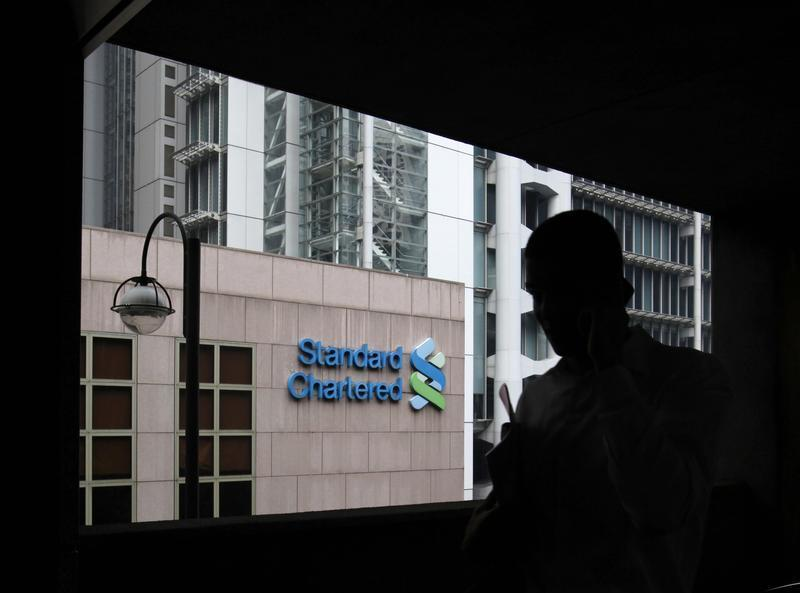 A man walks on a footbridge connected to the Standard Chartered headquarters in Hong Kong