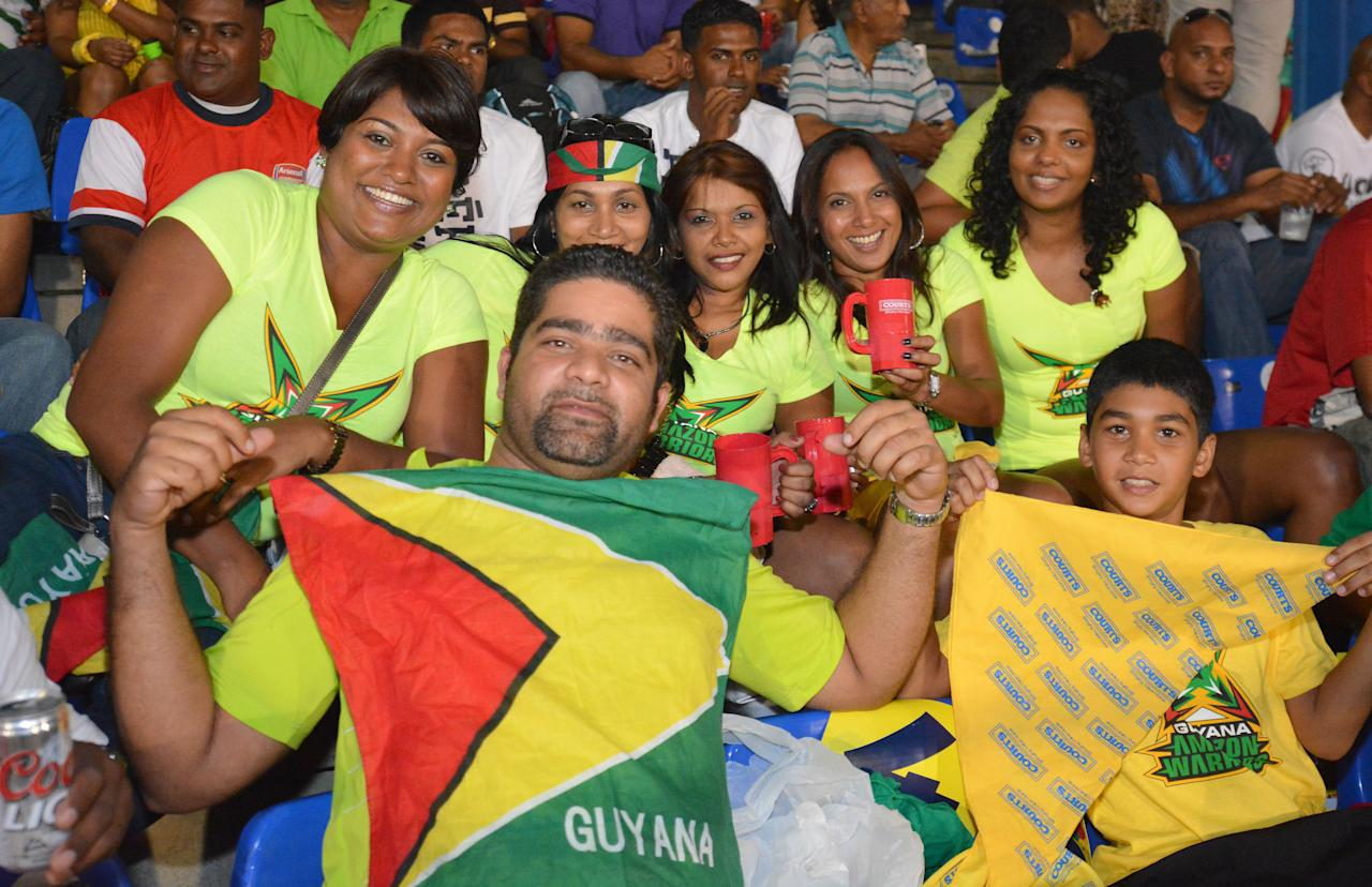 PORT OF SPAIN, TRINIDAD AND TOBAGO - AUGUST 24: Fans cheer their team during the Final of the Cricket Caribbean Premier League between Guyana Amazon Warriors v Jamaica Tallawahs at Queen's Park Oval on August 24, 2013 in Port of Spain, Trinidad and Tobago. (Photo by Lloyd Pierre/Getty Images Latin America for CPL)