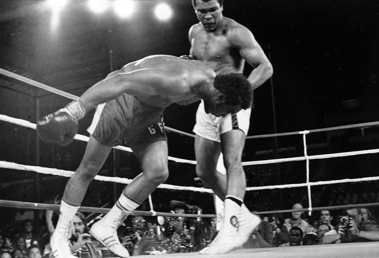 FILE - In this Oct. 30, 1974, file photo, challenger Muhammad Ali watches as defending world champion George Foreman goes down to the canvas in the eighth round of their WBA/WBC championship boximg match in Kinshasa, Zaire. Foreman was counted out by the referee and Ali regained the world heavyweight crown by KO in the bout dubbed 'Rumble in the Jungle.' Ali turns 70 on Jan. 17, 2012. (AP Photo/File)