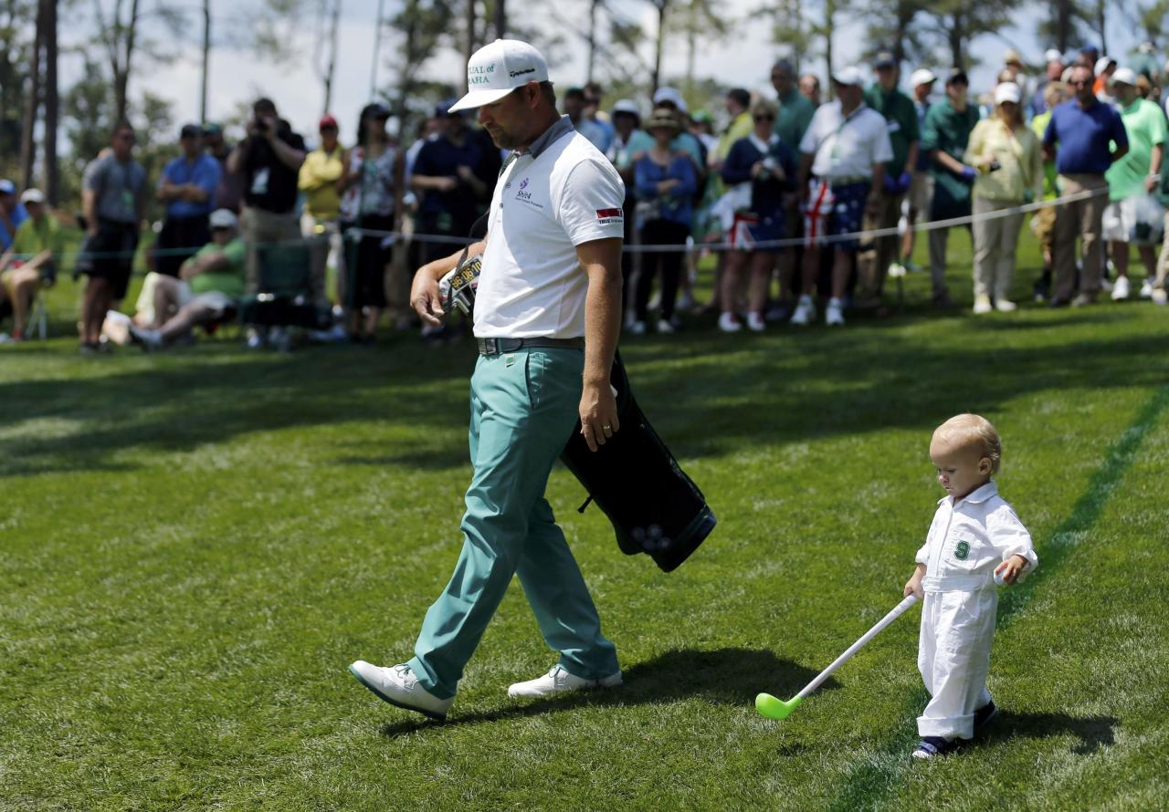 U.S. golfer Ryan Moore and his son Tucker (R) walk along the third hole during the Par 3 contest ahead of the Masters golf tournament at the Augusta National Golf Club in Augusta, Georgia April 9, 2014. REUTERS/Mike Blake (UNITED STATES - Tags: SPORT GOLF)