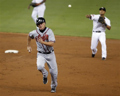 Atlanta Braves' Chipper Jones, foreground, is thrown out by Miami Marlins second baseman Donovan Solano as he runs back to first base after a sacrifice fly by Freddie Freeman during the third inning of a baseball game, Wednesday, Sept. 19, 2012, in Miami. Martin Prado scored on the play. (AP Photo/Wilfredo Lee)