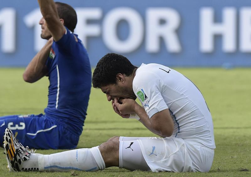Uruguay forward Luis Suarez (R) puts his hand to his mouth after clashing with Italy's defender Giorgio Chiellini during a Group D football match between Italy and Uruguay at the Dunas Arena in Natal during the 2014 FIFA World Cup on June 24, 2014