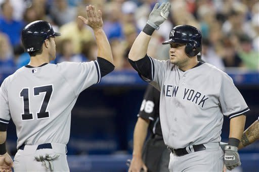 New York Yankees' Casey McGehee, right, celebrates with Jayson Nix after hitting a three run homer off Toronto Blue Jays pitcher Aaron Laffey during the  fourth inning of a baseball game in Toronto on Saturday, Aug. 11 , 2012. (AP Photo/The Canadian Press, Chris Young)