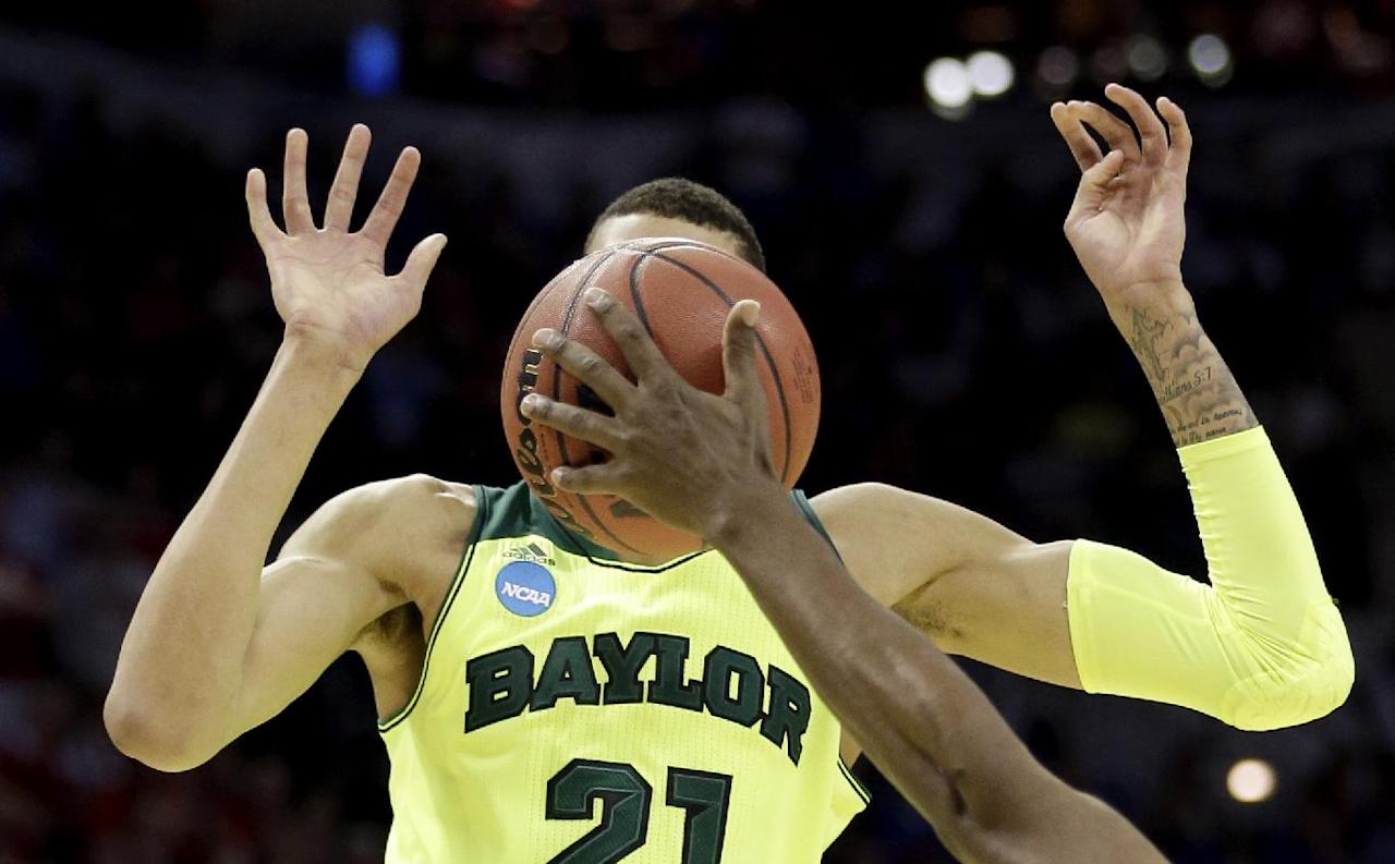 Baylor's Isaiah Austin (21) has his face covered by the ball as Nebraska's Leslee Smith's arm reaches for the ball during the second half of a second-round game in the NCAA college basketball tournament Friday, March 21, 2014, in San Antonio. Baylor won 74-60. (AP Photo/David J. Phillip)