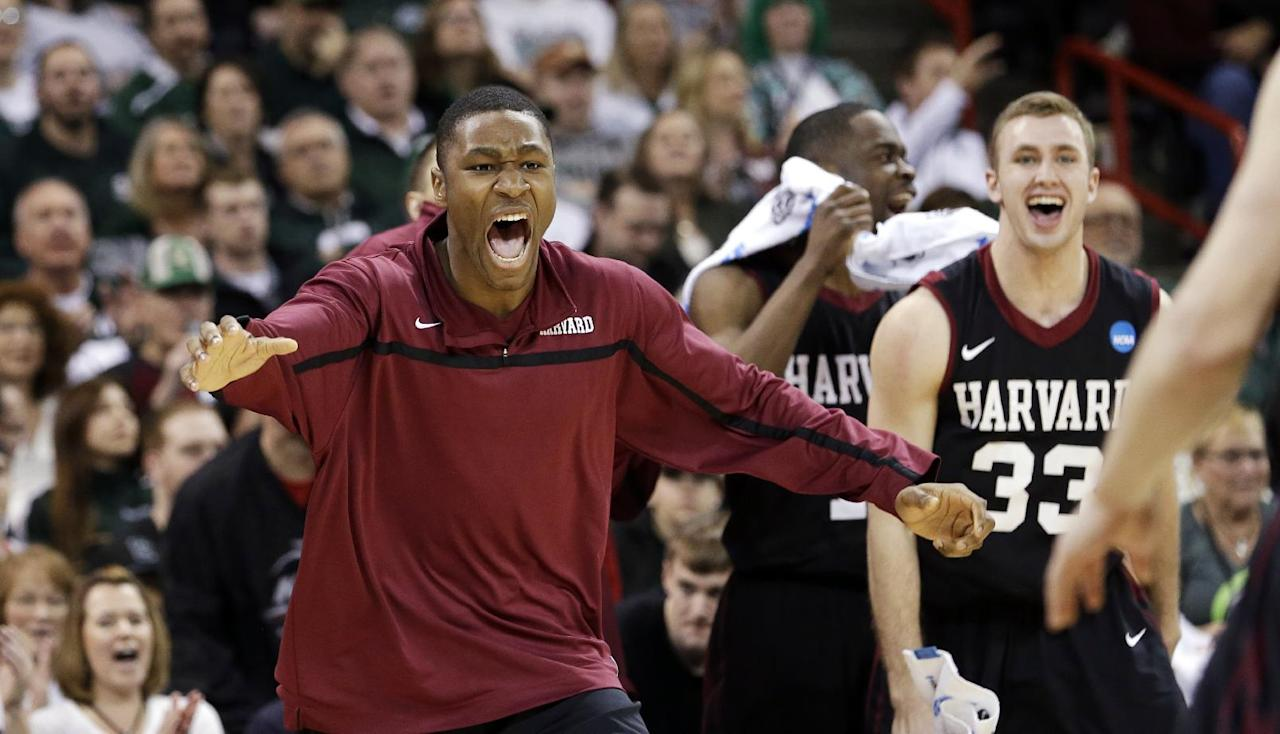 Harvard players rush from the bench to greet teammates after beating Cincinnati in the second round of the NCAA college basketball tournament in Spokane, Wash., Thursday, March 20, 2014. Harvard won 61-57. (AP Photo/Elaine Thompson)