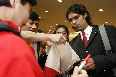 SC Internacional's Fernandao of Brazil signs an autograph for fans on his arrival for the FIFA Club World Cup at Narita International Airport near Tokyo