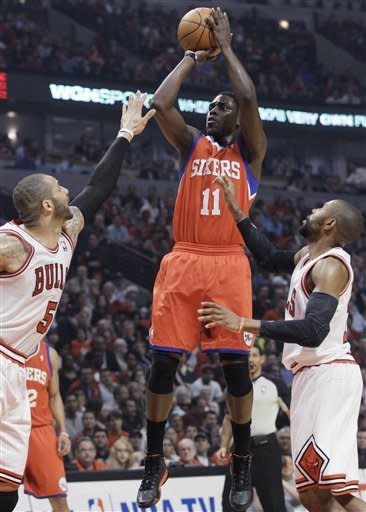 Philadelphia 76ers guard Jrue Holiday (11) shoots between Chicago Bulls forward Carlos Boozer (5) and guard C.J. Watson during the first quarter of Game 5 in an NBA basketball first-round playoff series, in Chicago on Tuesday, May 8, 2012. (AP Photo/Nam Y. Huh)