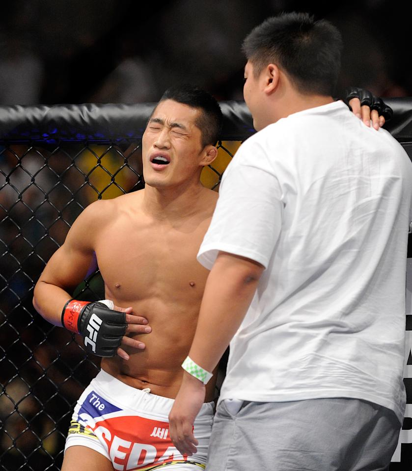 Dong Hyun Kim, left, is assisted by a team member after losing by TKO to Demian Maia during the first round their UFC 148 welterweight fight at the MGM Grand Garden Arena, Saturday, July 7, 2012, in Las Vegas. (AP Photo/David Becker)