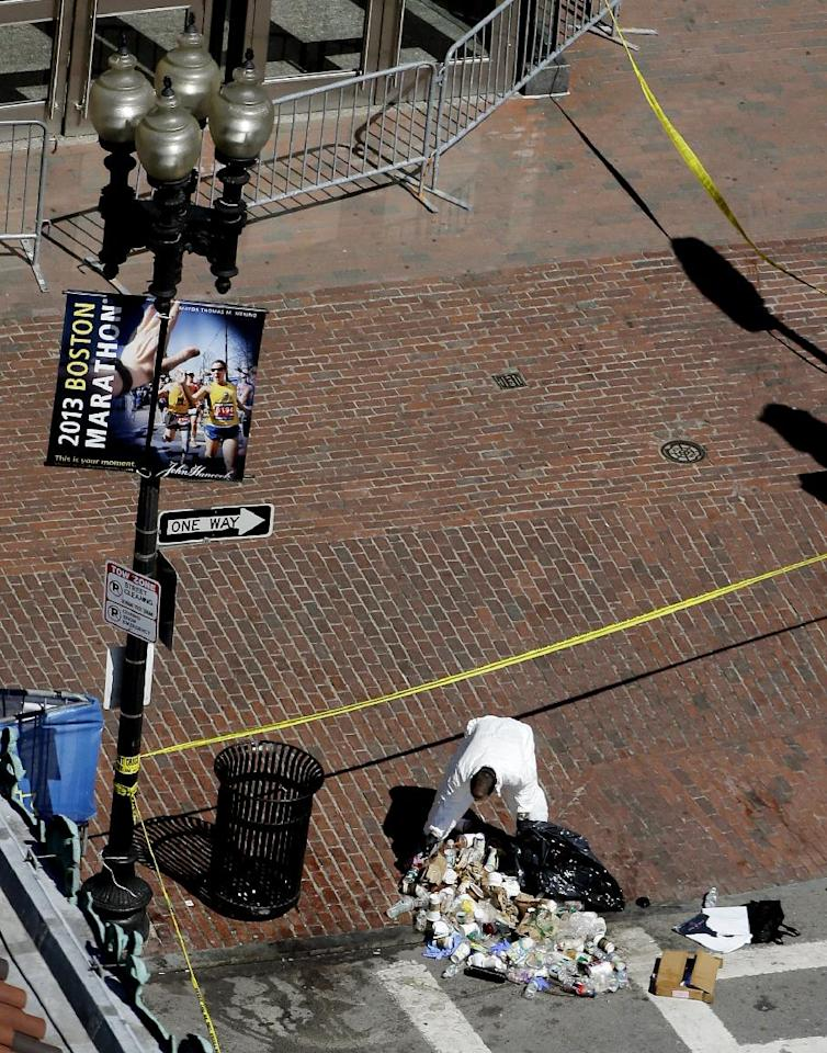 An investigator combs through trash pulled from a vin just beyond the Boston Marathon finish line on Boylston Street, two days after two bombs exploded just before the finish line, Wednesday, April 17, 2013, in Boston. Authorities investigating the deadly bombings have recovered a piece of circuit board that they believe was part of one of the explosive devices, and also found the lid of a pressure cooker that apparently was catapulted onto the roof of a nearby building, an official said Wednesday. (AP Photo/Julio Cortez)