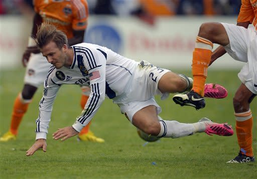 Los Angeles Galaxy midfielder David Beckham takes a fall during the first half of their MLS Cup soccer match against the Houston Dynamo, Saturday, Dec. 1, 2012, in Carson, Calif. (AP Photo/Mark J. Terrill)