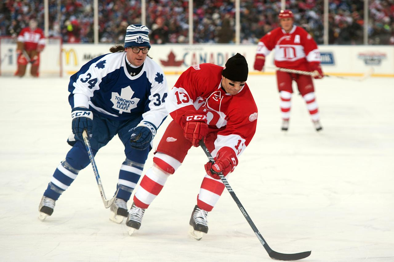 Dec 31, 2013; Detroit, MI, USA; Detroit Red Wings former forward Slava Kozlov (13) skates up ice against Toronto Maple Leafs former defenseman Bryan Berard (34) during the Alumni Showdown as part of the Winter Classic at Comerica Park. (Tim Fuller-USA TODAY Sports)