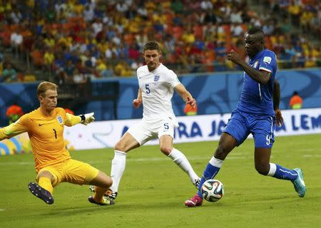 England's Joe Hart and Gary Cahill fight for the ball against Italy's Mario Balotelli during their 2014 World Cup Group D soccer match at the Amazonia arena