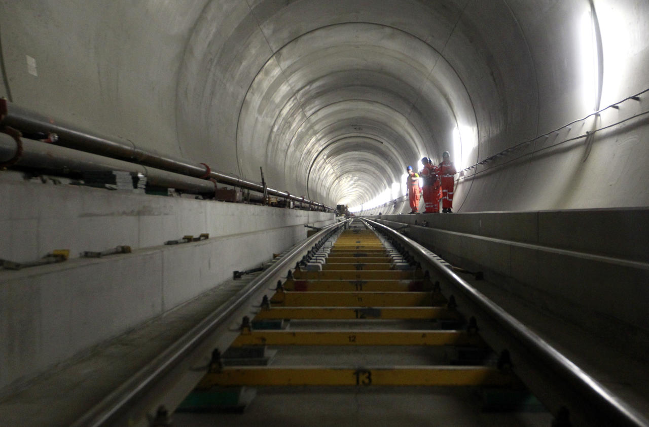 Journalists stand beside rail tracks at the construction site in the NEAT Gotthard Base tunnel near Sedrun April 2, 2013. Crossing the Alps, the world's longest train tunnel should become operational at the end of 2016. The project consists of two parallel single track tunnels, each of a length of 57 km (35 miles) REUTERS/Arnd Wiegmann (SWITZERLANDBUSINESS TRAVEL - Tags: TRAVEL BUSINESS EMPLOYMENT CONSTRUCTION) - RTXY5OX