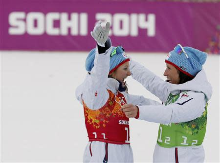 Winners Norway's Oestberg and Bjoergen embrace at the flower ceremony for the women's cross-country team sprint classic during the 2014 Sochi Winter Olympics