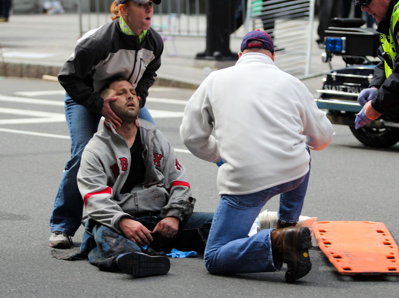 In this photo provided by The Daily Free Press and Kenshin Okubo, people assist an injured after an explosion at the 2013 Boston Marathon in Boston, Monday, April 15, 2013. Two explosions shattered the euphoria of the Boston Marathon finish line on Monday, sending authorities out on the course to carry off the injured while the stragglers were rerouted away from the smoking site of the blasts. (AP Photo/The Daily Free Press, Kenshin Okubo) MANDATORY CREDIT