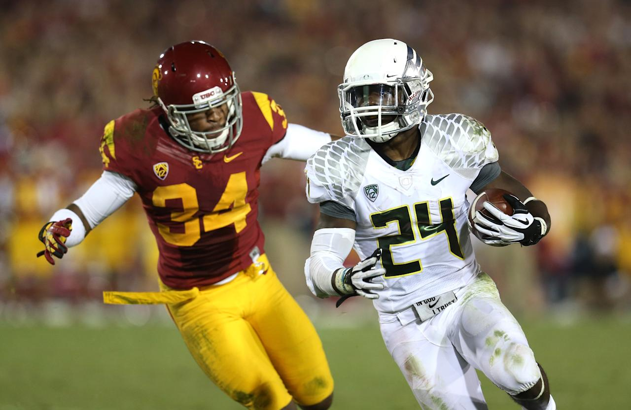 LOS ANGELES, CA - NOVEMBER 03:  Running back Kenjon Barner #24 of the Oregon Ducks carries the ball against linebacker Tony Burnett #34 of the USC Trojans in the third quarter at the Los Angeles Memorial Coliseum on November 3, 2012  in Los Angeles, California.  Oregon won 62-51.  (Photo by Stephen Dunn/Getty Images)