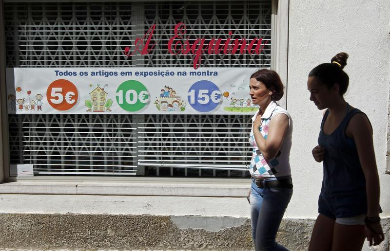 Women walk past a shop window announcing sale prices along a street in Mafra, north of Lisbon