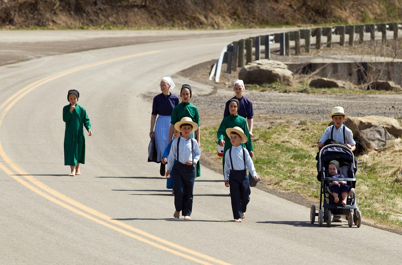 Wilma Mullet and her family walk to the school house for the final day of class on Tuesday, April 9, 2013 in Bergholz, Ohio. Mullet and other Amish families gathered for a farewell celebration before members of the sect depart for prison following convictions in a beard cutting scandal. (AP Photo/Scott R. Galvin)