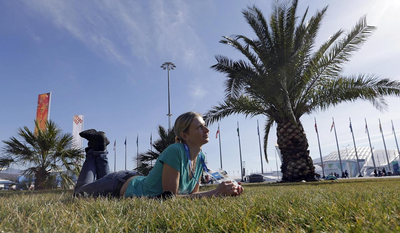 Oxsana Kharitonova lyes on the grass while posing for a photograph with friends on a sunny warm day at the 2014 Winter Olympics, Wednesday, Feb. 12, 2014, in Sochi, Russia. (AP Photo/David J. Phillip )