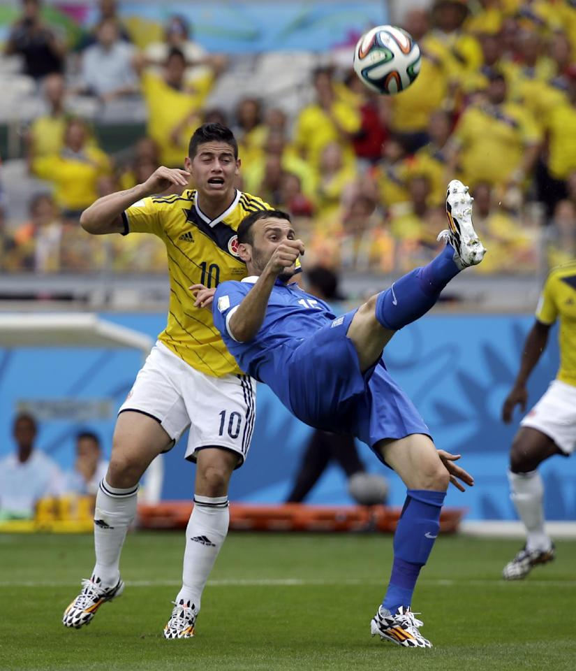 Greece's Vasilis Torosidis, right, kicks the ball over Colombia's James Rodriguez during the group C World Cup soccer match between Colombia and Greece at the Mineirao Stadium in Belo Horizonte, Brazil, Saturday, June 14, 2014.  (AP Photo/Fernando Vergara)
