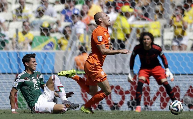 Netherlands' Arjen Robben, right, goes down under a challenge from Mexico's Hector Moreno during the World Cup round of 16 soccer match between the Netherlands and Mexico at the Arena Castelao in Fortaleza, Brazil, Sunday, June 29, 2014