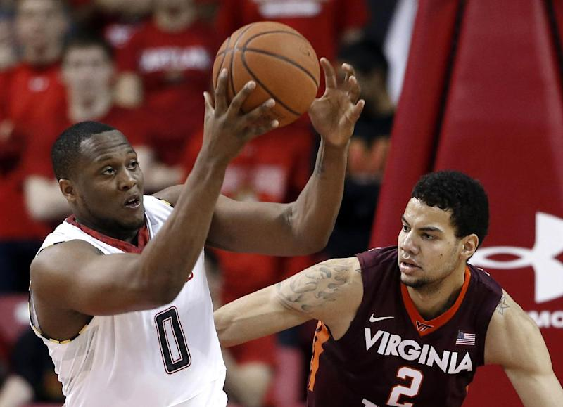 Maryland forward Charles Mitchell, left, tries to hold on to a rebound in front of Virginia Tech forward Joey Van Zegeren during the first half of an NCAA college basketball game in College Park, Md., Tuesday, March 4, 2014