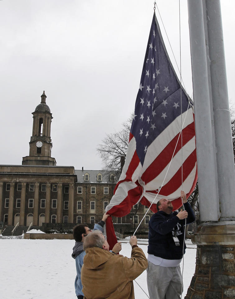 John Emigh, left, Darren Dixon, and Terrence Krumrine, back right, raise an American flag to half staff in honor of former Penn State Coach Joe Paterno in front of Old Main on the Penn State campus Monday, Jan. 23, 2012 in State College, Pa. Paterno, a sainted figure at Penn State for almost half a century but scarred forever by the scandal involving his one-time heir apparent, died Sunday, Jan. 22, 2012 in State College. He was 85. .(AP Photo/Alex Brandon)
