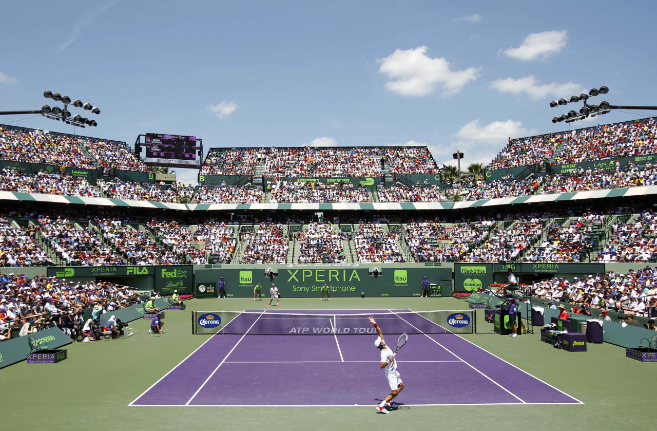 Novak Djokovic, foreground, of Serbia, serves to Andy Murray, of Great Britain, during the men's singles final match at the Sony Ericsson Open tennis tournament on Sunday, April 1, 2012, in Key Biscayne, Fla. (AP Photo/Wilfredo Lee)