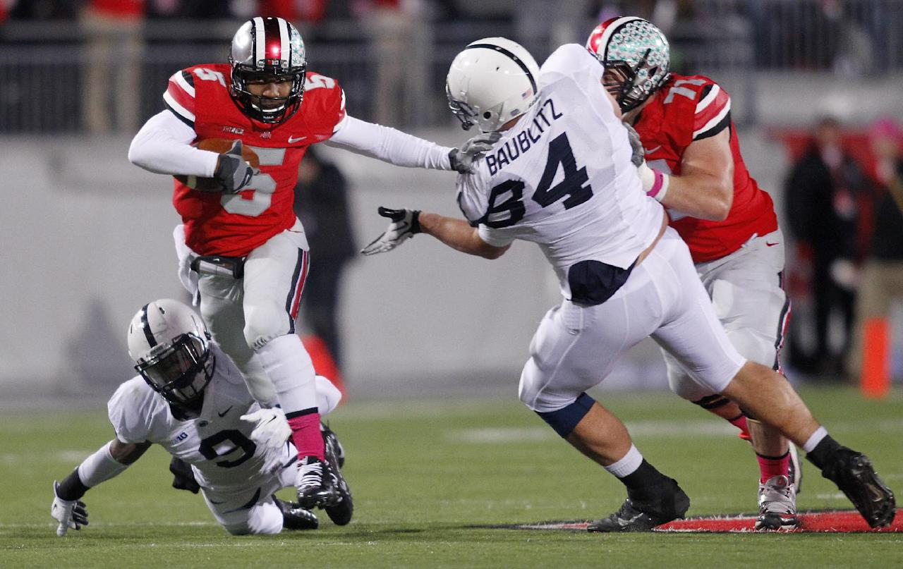 Ohio State quarterback Braxton Miller, top left, escapes the grasp of Penn State cornerback Jordan Lucas, bottom left, as Ohio State offensive lineman Corey Linsley, right, blocks Penn State defensive tackle Kyle Baublitz during the first quarter of an NCAA college football game Saturday, Oct. 26, 2013, in Columbus, Ohio. (AP Photo/Paul Vernon)