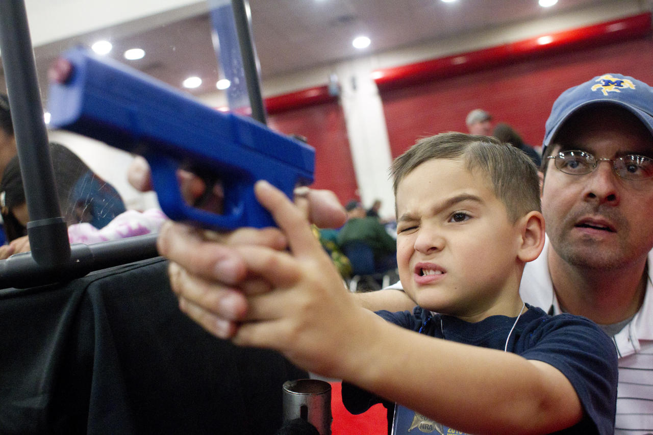 Heath Bryant of Cypress assists his son, Tate, 5, to shoot a target using a video game-style of gun at an exhibit booth  during NRA Youth Day events at the National Rifle Association's 142 Annual Meetings and Exhibits in the George R. Brown Convention Center Sunday, May 5, 2013, in Houston. More than 70,000 are expected to attend the event with more than 500 exhibitors represented. (AP Photo/Houston Chronicle, Johnny Hanson)