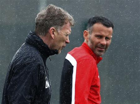 File photo of Manchester United's manager Moyes walking past Giggs during a training session at the club's Carrington training complex in Manchester
