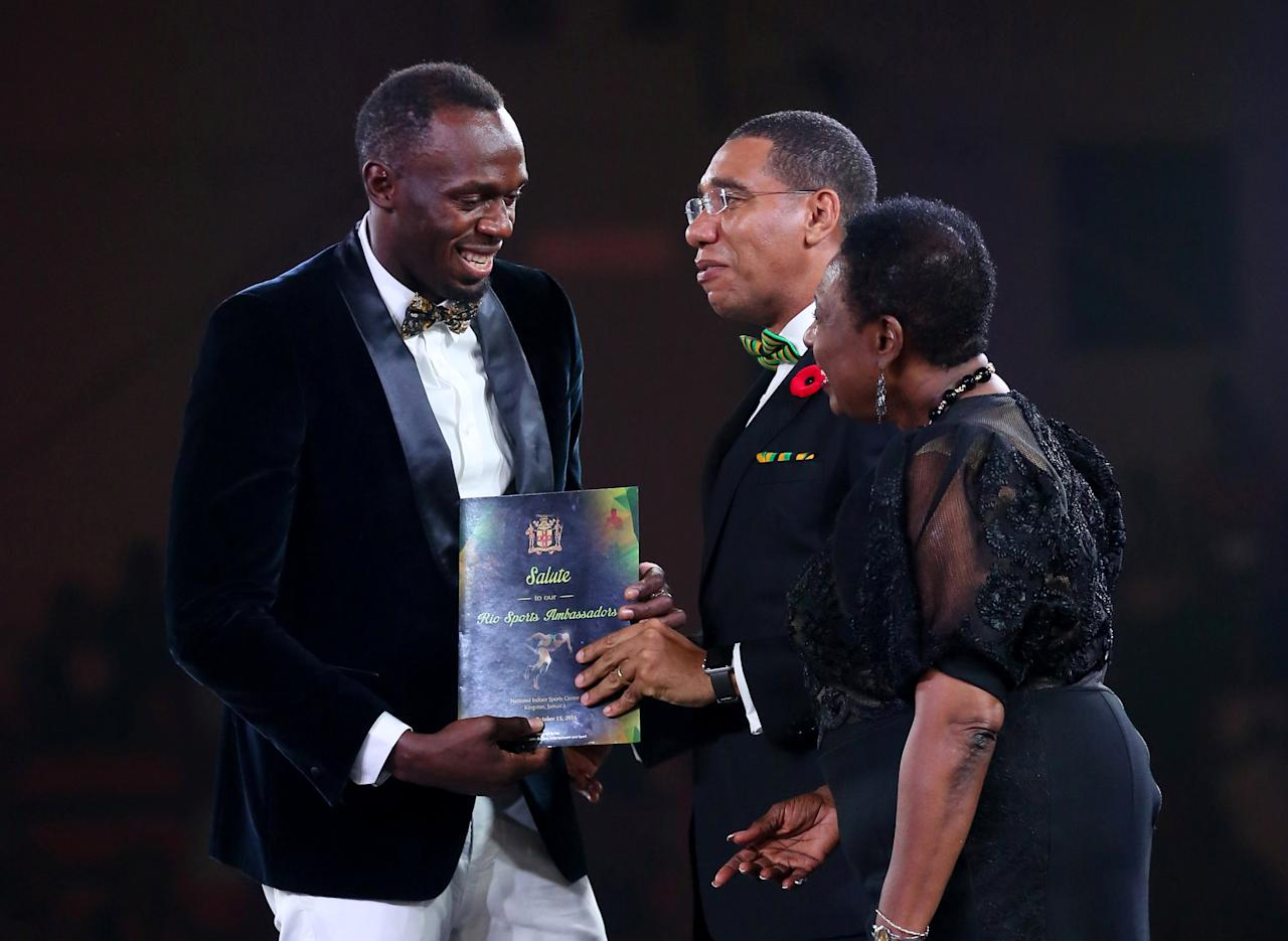 Jamaican Olympic gold medallist Usain Bolt (L) receives an award from Jaimaica's Prime Minister Andrew Holness (C) and Minister of Culture, Gender, Entertainment and Sport Olivia Grange during an event in Kingston, Jamaica, October 15, 2016. Picture taken October 15, 2016.  REUTERS/Gilbert Bellamy