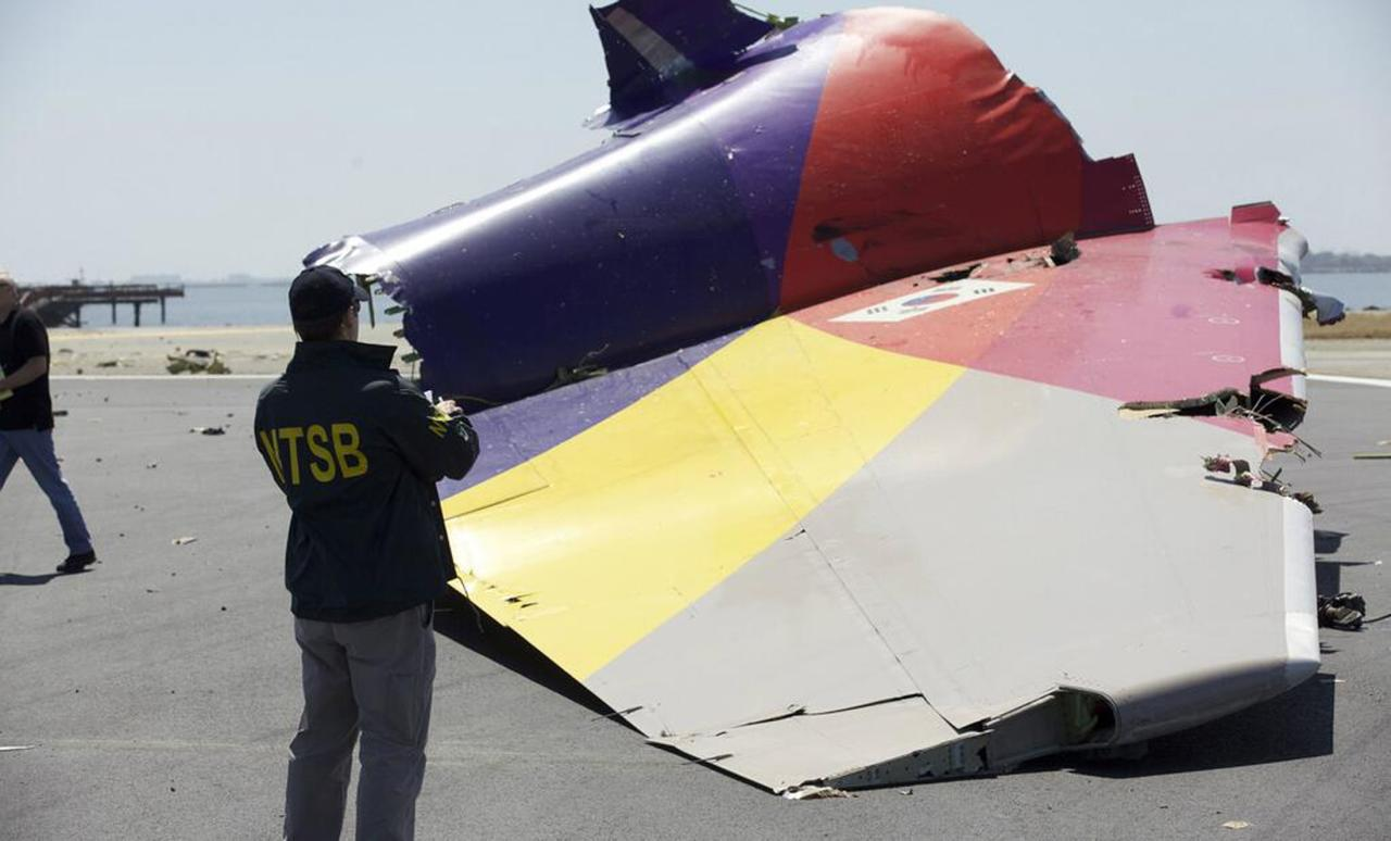 A National Transportation Safety Board (NTSB) investigator looks at the tail section of the Asiana Airlines Flight 214 that crashed at San Francisco International Airport in San Francisco, California in this handout file photo released on July 7, 2013. Pilots of the Asiana Airlines Inc plane were aware the plane was traveling too slowly and tried to correct it in the final seconds before impact, according to documents released on December 11, 2013 by U.S. aviation safety investigators. REUTERS/NTSB/Handout via Reuters/Files (UNITED STATES - Tags: TRANSPORT DISASTER) 