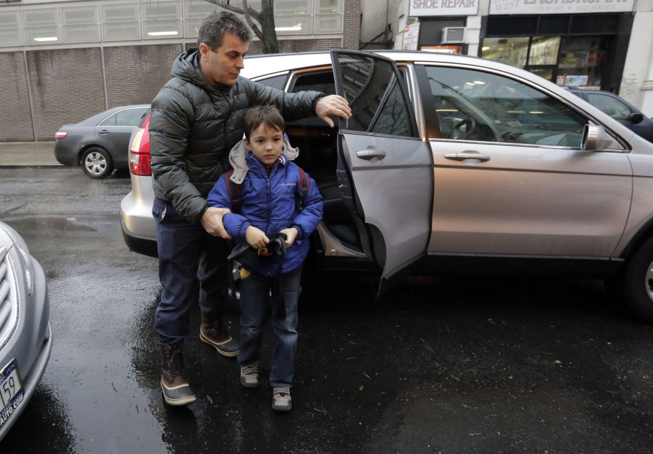 Alex Ndoka, left, accompanies Henry Ndoka, who usually rides school bus to Public School 9, as they arrive for school by car on New York's Upper West Side, Wednesday, Jan. 16, 2013. More than 8,000 New York City school bus drivers and matrons went on strike over job protection Wednesday morning, leaving some 152,000 students, many disabled, trying to find other ways to get to school. (AP Photo/Richard Drew)