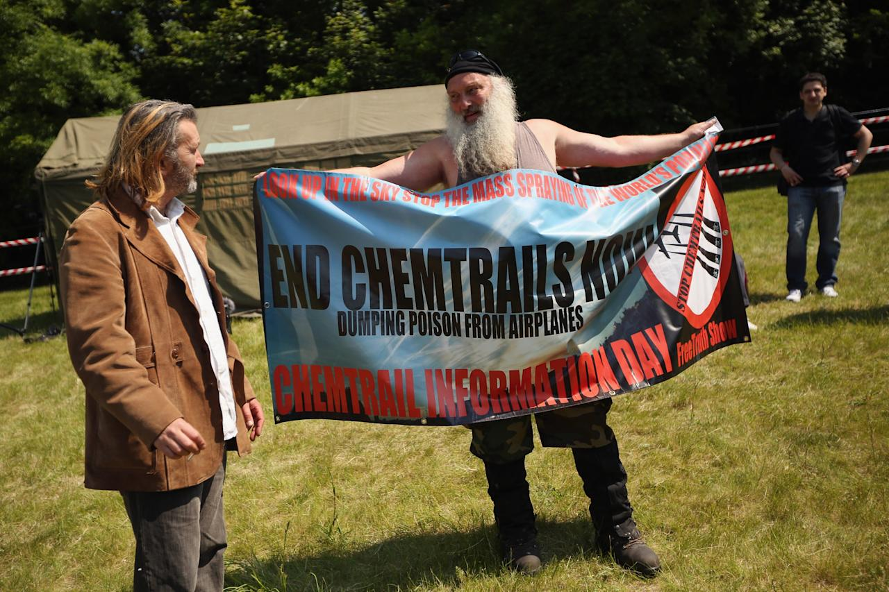 "WATFORD, ENGLAND - JUNE 06: A man demonstrates against ""Chemtrails"" in a protester encampment outside The Grove hotel, which is hosting the annual Bilderberg conference, on June 6, 2013 in Watford, England. The traditionally secretive conference, which has taken place since 1954, is expected to be attended by politicians, bank bosses, businessman and European royalty. (Photo by Oli Scarff/Getty Images)"