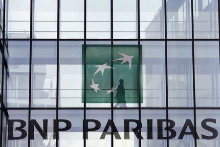 An employee walks behind the logo of BNP Paribas in a company's building in Issy-les-Moulineaux, near Paris