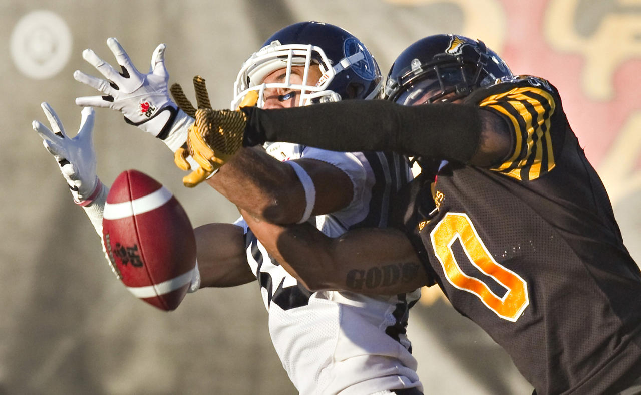 Hamilton Tiger-Cats Rico Murray (R) breaks up a pass to Toronto Argonauts Spencer Watt in the first half of their CFL football game in Guelph October 14, 2013. REUTERS/Fred Thornhill (CANADA - Tags: SPORT FOOTBALL TPX IMAGES OF THE DAY)