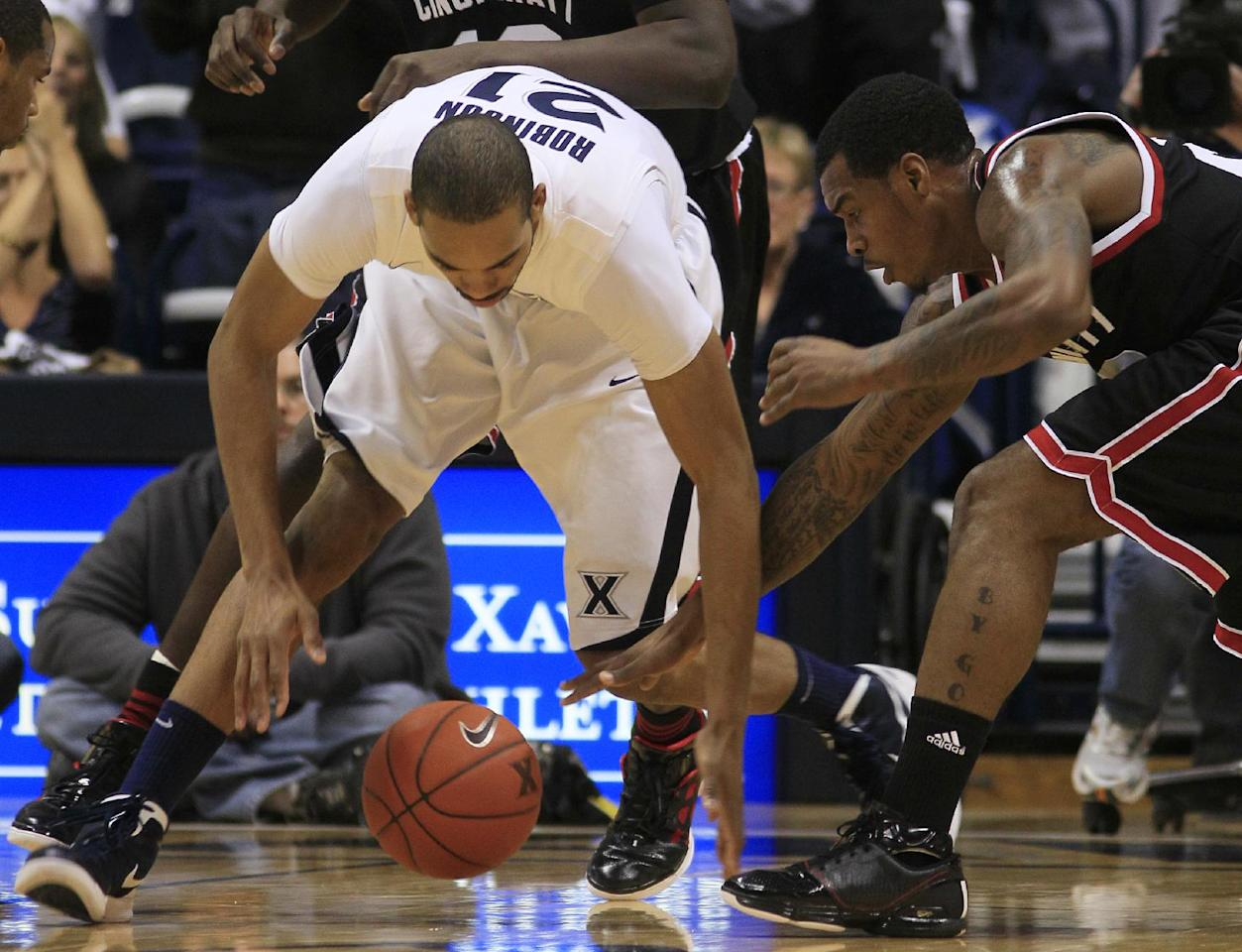 Cincinnati guard Sean Kilpatrick, right, chases a loose ball against Xavier forward Jeff Robinson (21) in the first half of an NCAA college basketball game, Saturday, Dec. 10, 2011, in Cincinnati. (AP Photo/Al Behrman)
