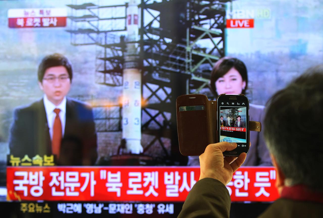 """South Korean man uses his smartphone to take a television screen reporting a news about North Korea's rocket launch at Seoul Railway Station in Seoul, South Korea, Wednesday, Dec. 12, 2012. North Korea fired a long-range rocket Wednesday in its second launch under its new leader, South Korean officials said, defying warnings from the U.N. and Washington only days before South Korean presidential elections. The letters on the screen read """" North Korea's rocket launch seems to be successful."""" (AP Photo/Ahn Young-joon)"""