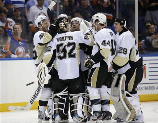 Pittsburgh Penguins, including defenseman Brooks Orpik (44), celebrate with goalie Tomas Vokoun (92), of the Czech Republic, after Orpik scored in overtime of Game 6 of the team's first-round NHL Stanley Cup playoff hockey series against the New York Islanders in Uniondale, N.Y., Saturday, May 11, 2013. The Penguins won 4-3, and advanced to the Eastern Conference semifinals. (AP Photo/Kathy Willens)