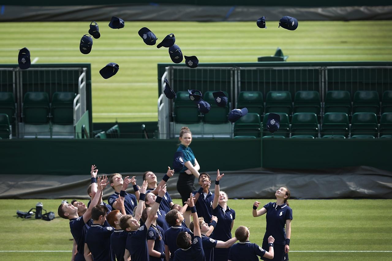 LONDON, ENGLAND - JUNE 27: Ball boys and girls throw their hats in the air during a photo shoot on day four of the Wimbledon Lawn Tennis Championships at the All England Lawn Tennis and Croquet Club on June 27, 2013 in London, England. (Photo by Peter Macdiarmid/Getty Images)