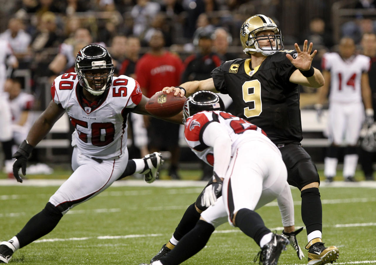 New Orleans Saints quarterback Drew Brees (9) throws a touchdown pass as Atlanta Falcons middle linebacker Curtis Lofton (50) and cornerback Brent Grimes (20) close in during the third quarter of an NFL football game in New Orleans, Monday, Dec. 26, 2011. (AP Photo/Rusty Costanza)