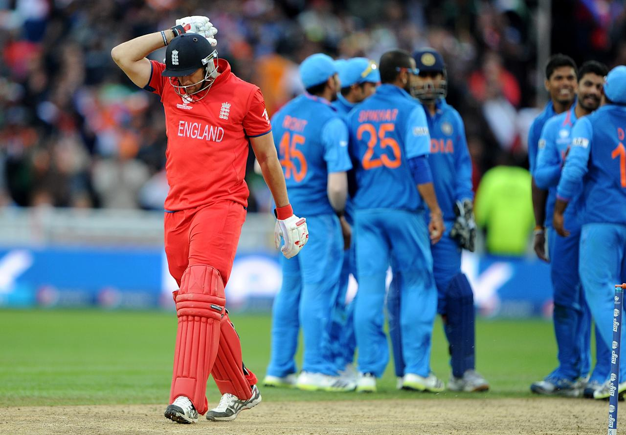 England's Tim Bresnan (L) reacts after being run out during the 2013 ICC Champions Trophy Final cricket match between England and India at Edgbaston in Birmingham, central England on 23, June 2013.  India scored 129 runs for the loss of seven wickets after the rain delayed match was reduced reduced to the bare minimum of 20 overs per side required to produced a result.   AFP PHOTO/ANDREW YATES