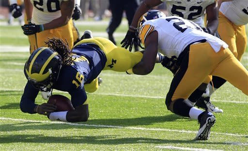 Michigan quarterback Denard Robinson (16) is upended by Iowa defensive back Nico Law (21) during the first quarter of an NCAA college football game at Michigan Stadium in Ann Arbor, Mich., Saturday, Nov. 17, 2012. (AP Photo/Carlos Osorio)