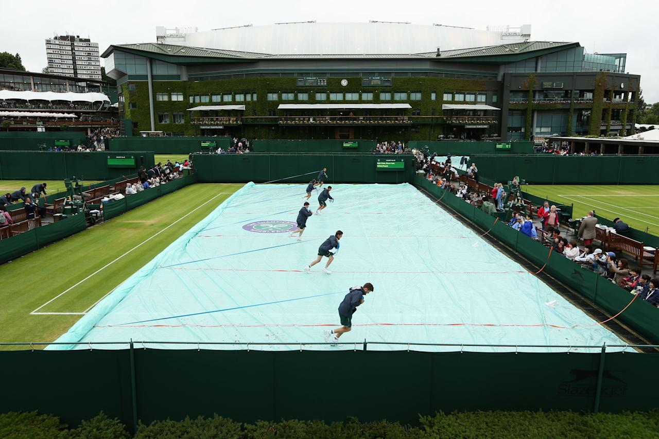 LONDON, ENGLAND - JUNE 28: The groundstaff remove the covers from court ten prior to play on day five of the Wimbledon Lawn Tennis Championships at the All England Lawn Tennis and Croquet Club on June 28, 2013 in London, England. (Photo by Clive Brunskill/Getty Images)