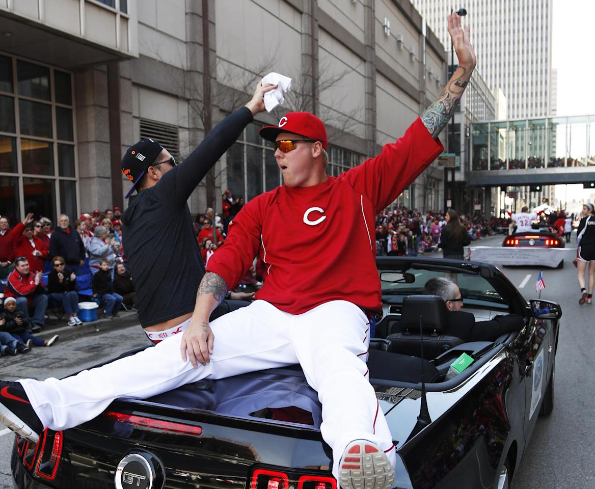 Cincinnati Reds starting pitcher Mat Latos rides on the back of a car during the annual opening day parade, Monday, March 31, 2014, in Cincinnati. The Cincinnati Reds play the St. Louis Cardinals. (AP Photo/David Kohl)