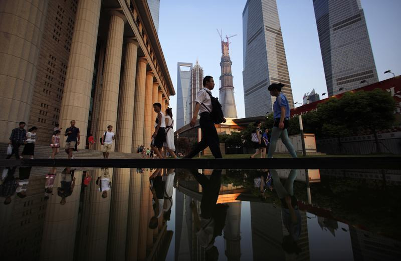 People walk to a subway station at the financial district of Pudong in Shanghai