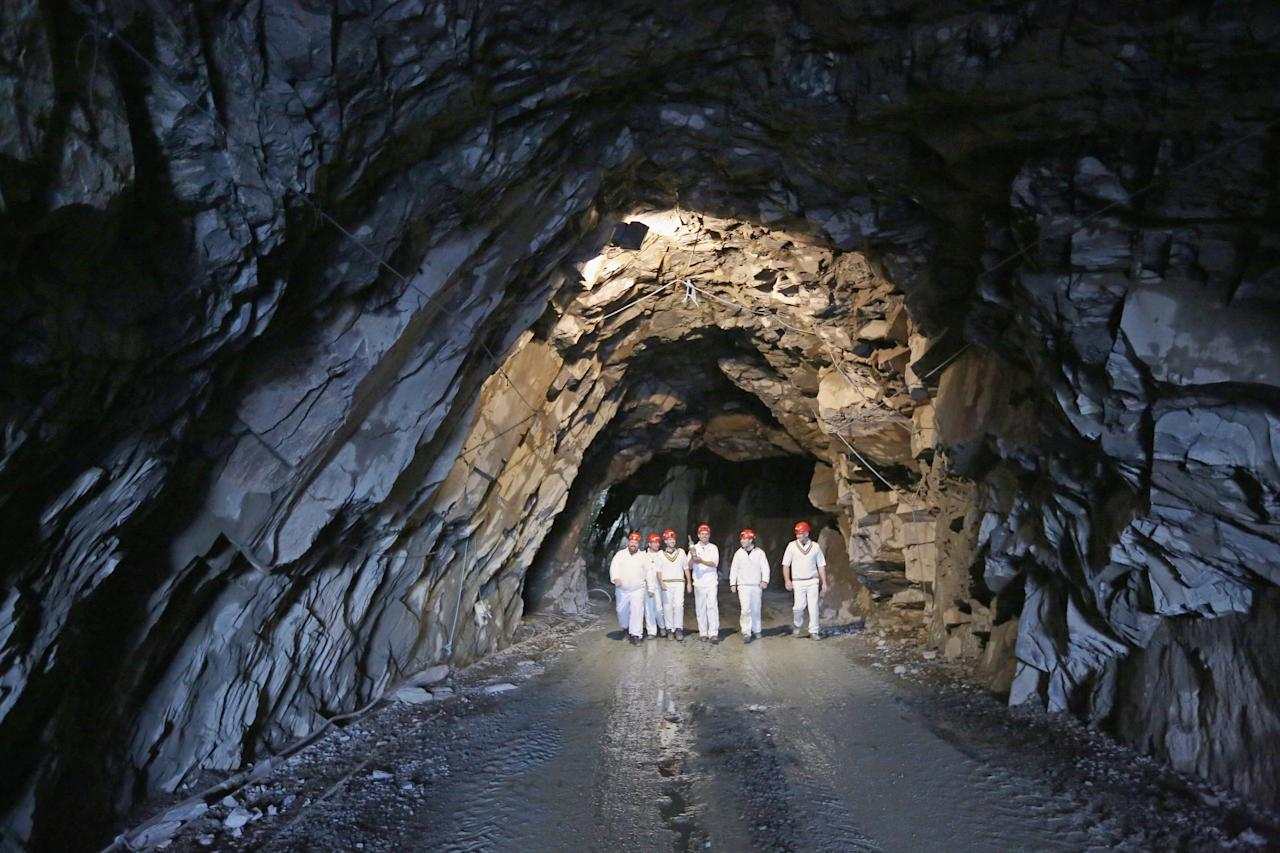 KESWICK, ENGLAND - DECEMBER 05:  Caldbeck cricket team walk from Honister Slate Mine with their trophy after winning the world's first underground cricket match on December 5, 2013 in Keswick, England. The Christmas fixture between Caldbeck and Threlkeld took part 600m (2,000ft) inside Fleetwith Pike at  Englands last working slate mine at Honister in the Lake District. The game is one of many unusual venues the teams have played in to raise money to fix Threlkeld Cricket Club's flood damaged ground. The match was won by Caldbeck Village.  (Photo by Christopher Furlong/Getty Images)